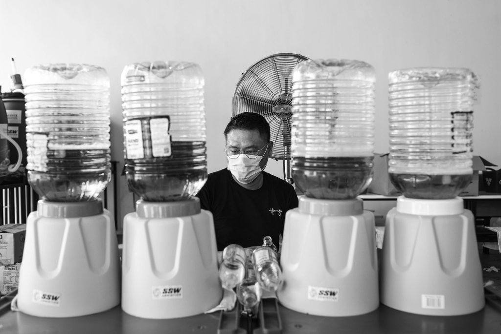 Don't try this at home. Harry's Singapore employee, Elmer Choo, 42, is an operations manager at the pub group. Pitching in at the MWC since April 11, he shows how he can fill up to four bottles at a time.