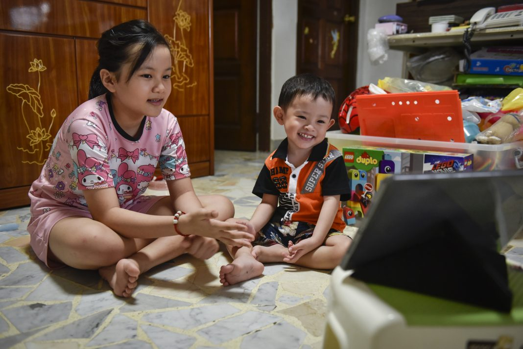 Tay Ming Jun, 3, being guided by his sister, Tay Wan Xuan, 10, as he watches educational programmes on an iPad at home. Extraordinary People helps provide speech therapy lessons online for Ming Jun.