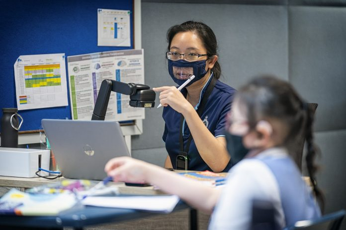 """Teachers at Canossian School don transparent masks to help students with hearing loss understand them better as they are given a """"window"""" to view facial expressions – an important part of speech reading."""
