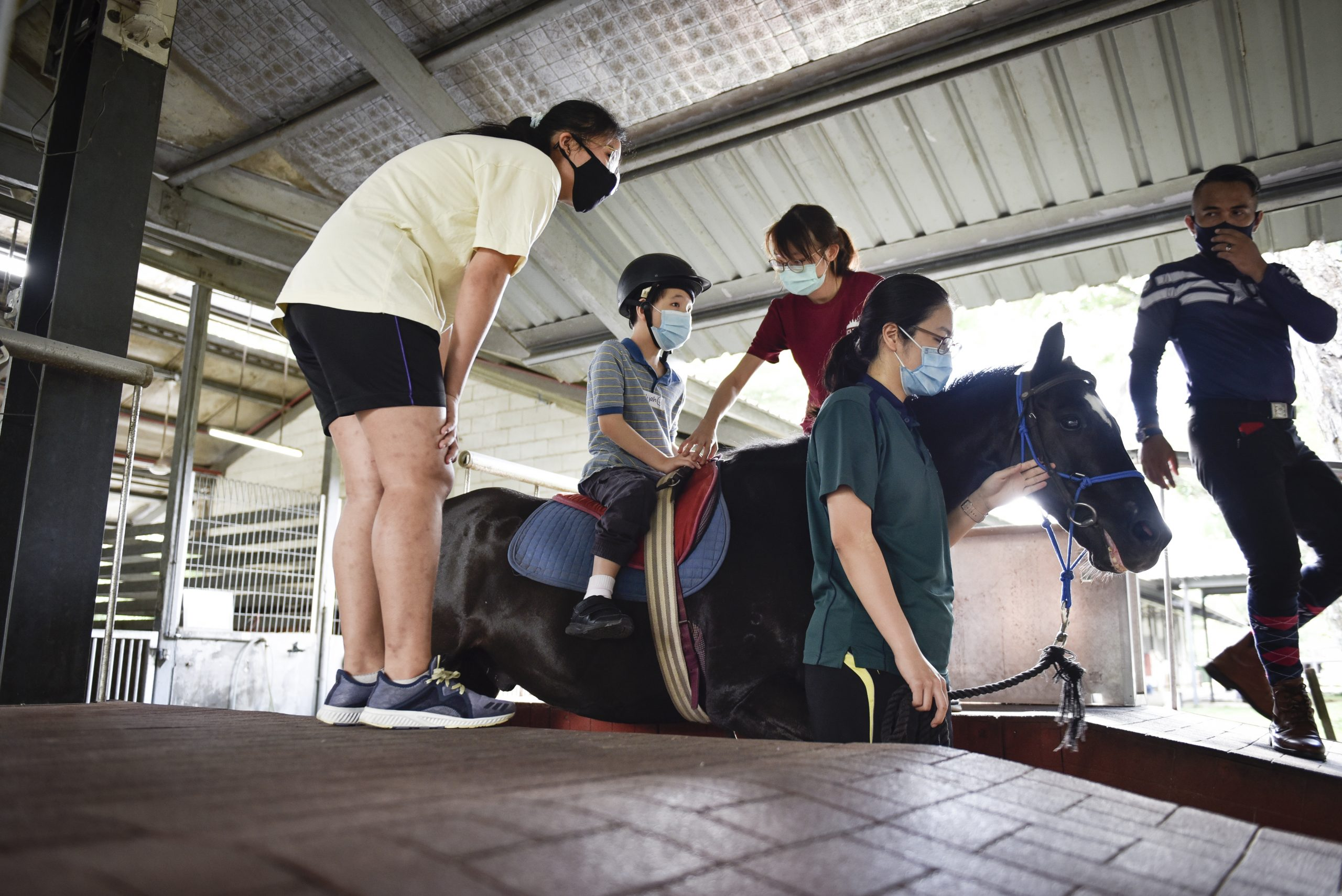 """Charlene Wong, 29, a volunteer with RDA Singapore (wearing green), is the leader who handles Elijah's horse, while interacting with Elijah during his session. """" I really like horses so being able to be at the stables while volunteering with children makes it a win-win situation, said Wong. """"My interest in volunteering has always been about empowering children with disabilities, so RDA is a great fit with the programme that it runs for the community."""""""