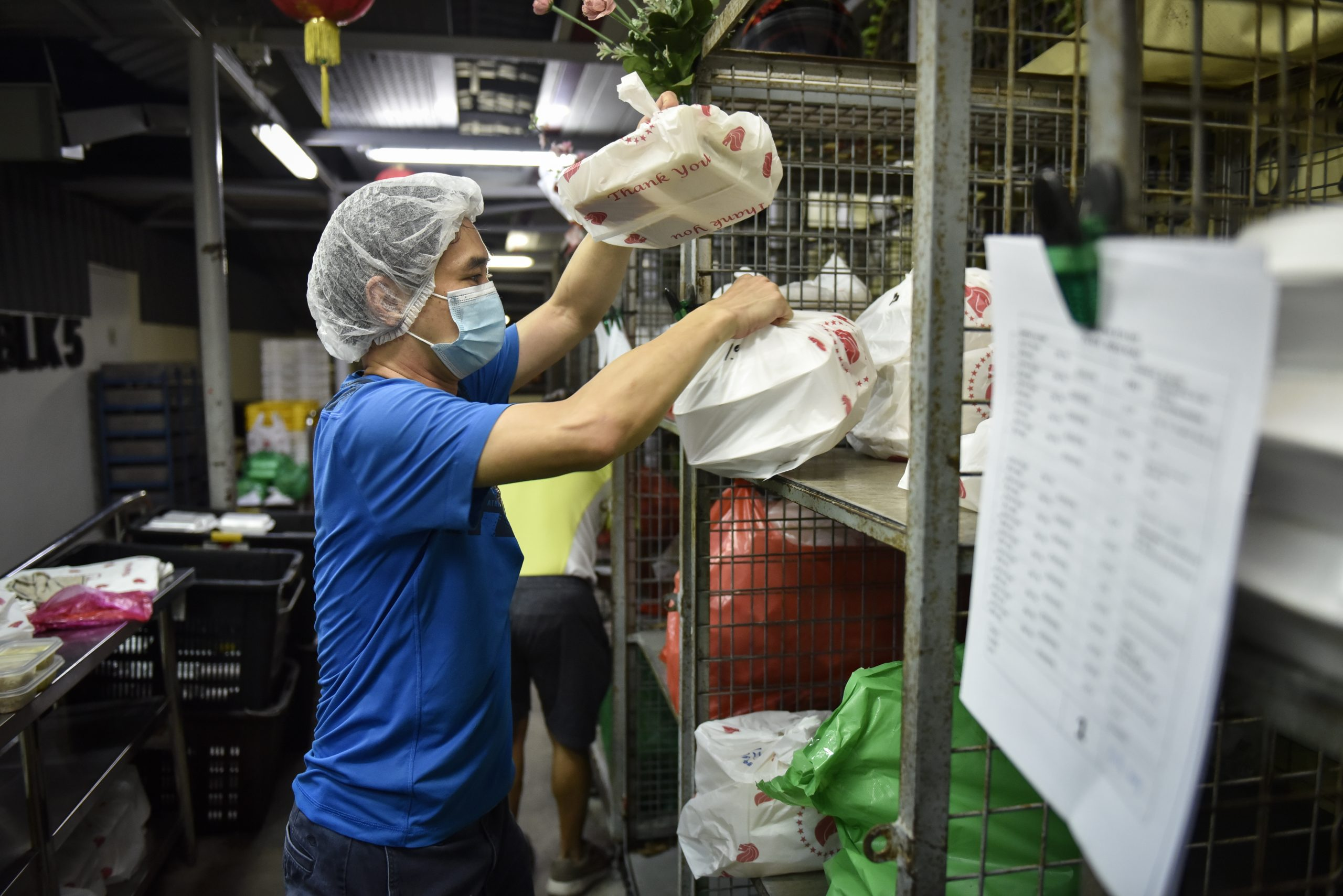 A volunteer sorts out the packets of food for loading into delivery vehicles.
