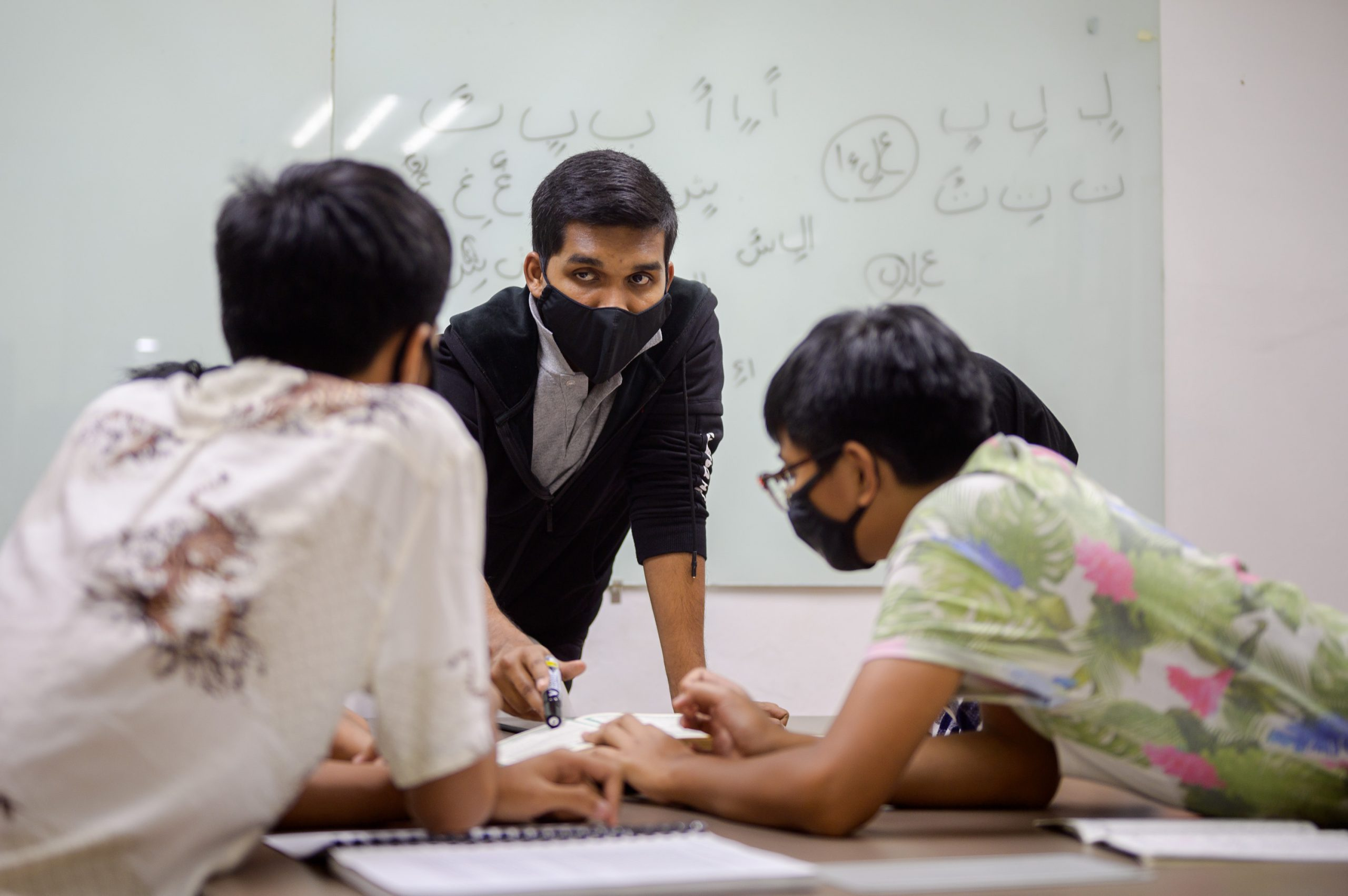 Beneficiaries have the opportunity to learn language and culture at Human HeartS. Volunteer Ali teaches the difference between Jawi and Arabic script to older youths.