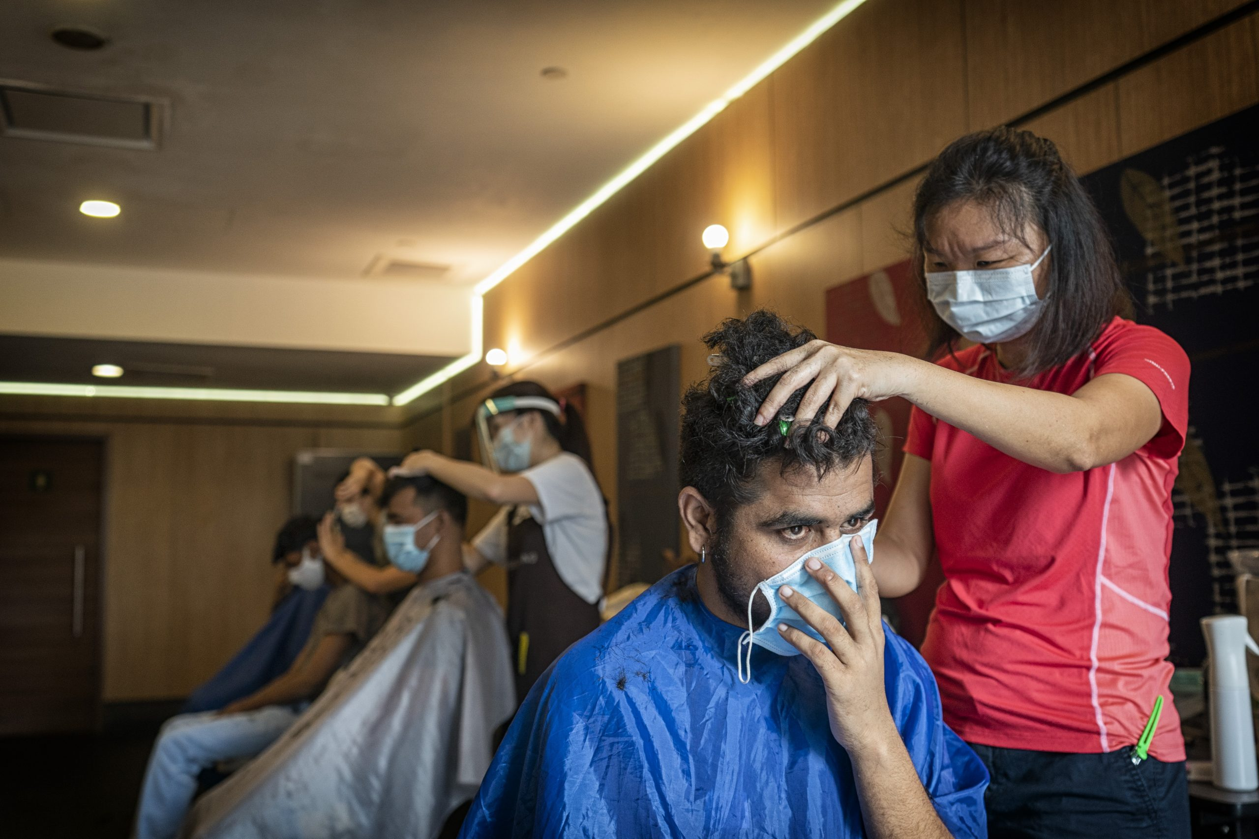 Trained hairdressers, volunteers from Backalley Barbers, offer their time to groom the migrant workers after months of dealing with overgrown locks.