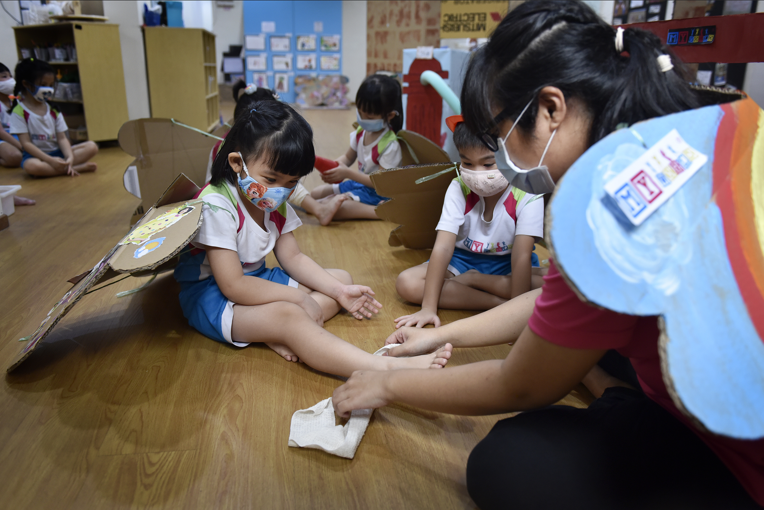 Preschool educator, Ms Danielle Jansen, 27, (right) teaches her K1 class about first-aid. To encourage the children to keep their wings on, some teachers wear them as well.