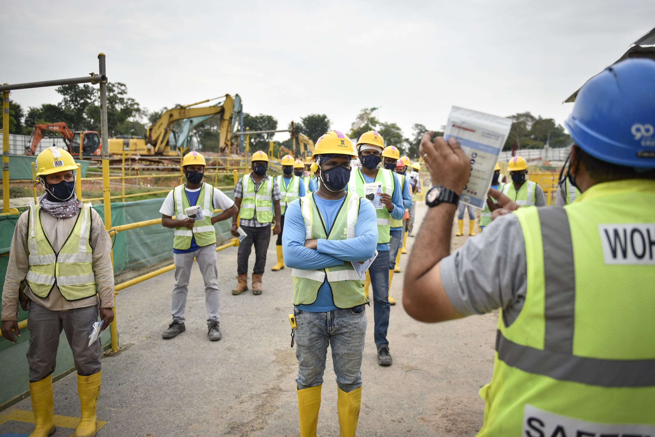 A site supervisor explains to workers that the reusable masks need only be washed once a week, instead of daily, and is reusable for up to 30 washes