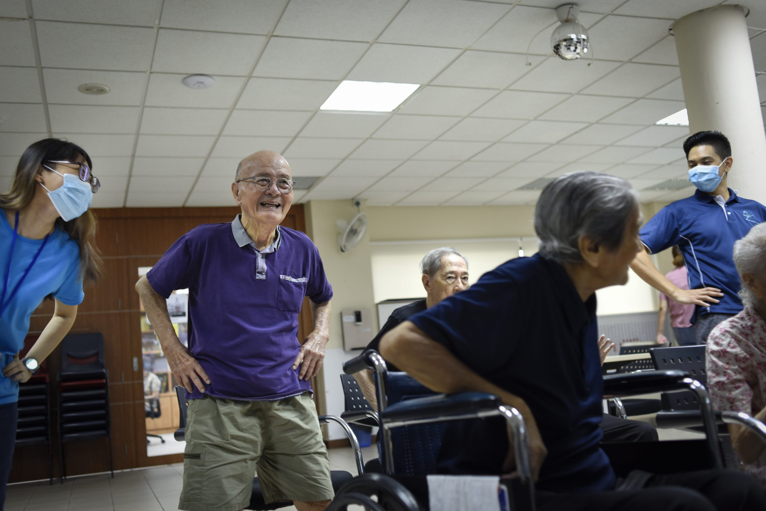 """Associate psychologist, Ms Nikki Goh (left), 25, encourages Mr Seow to dance along to """"Take Me Home, Country Roads"""". Ms Goh is one of the facilitators who plans and participates in the weekly online programmes"""