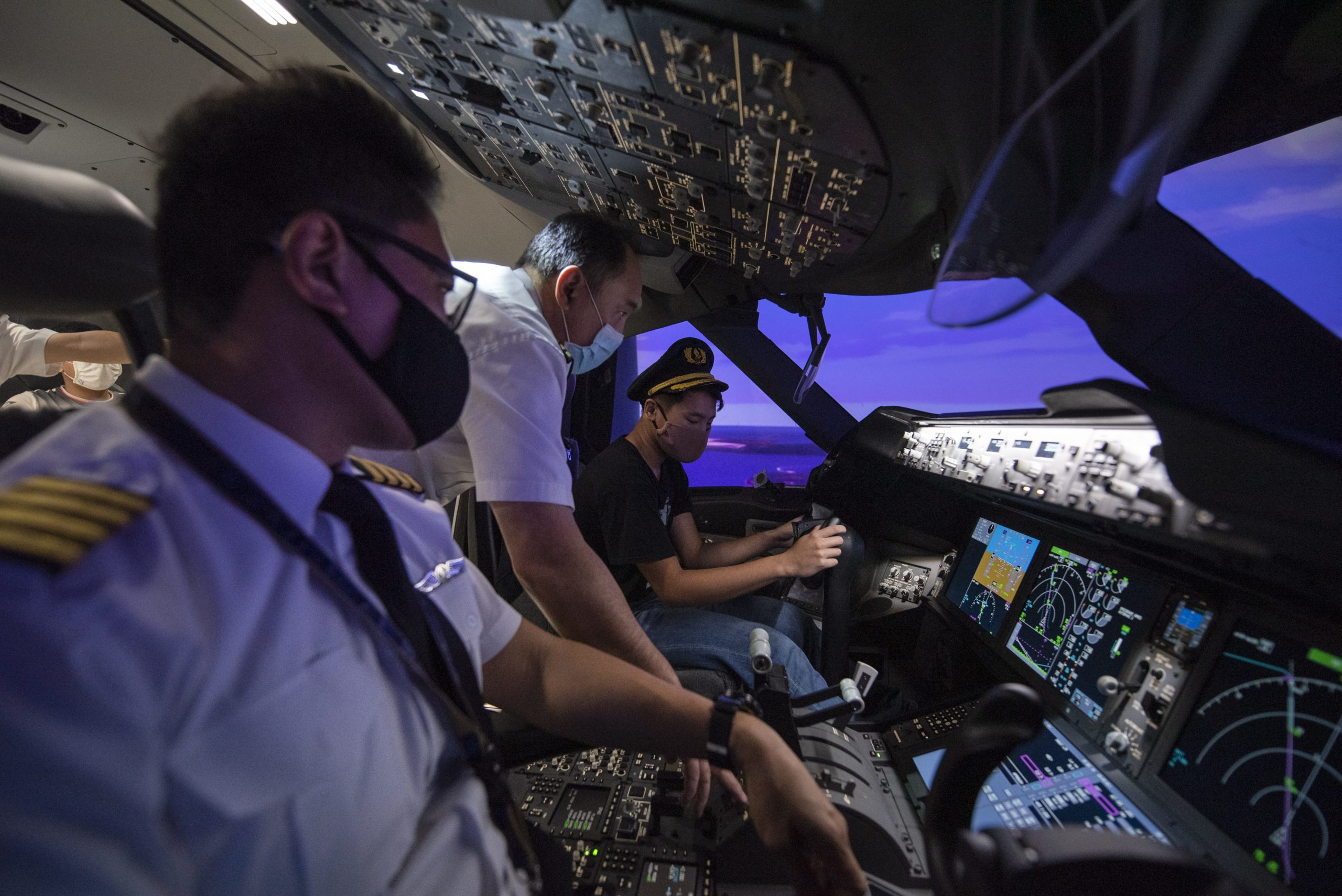 Two SIA pilots guide a participant of Inside Singapore Airlines inside the cockpit of a full flight simulator.