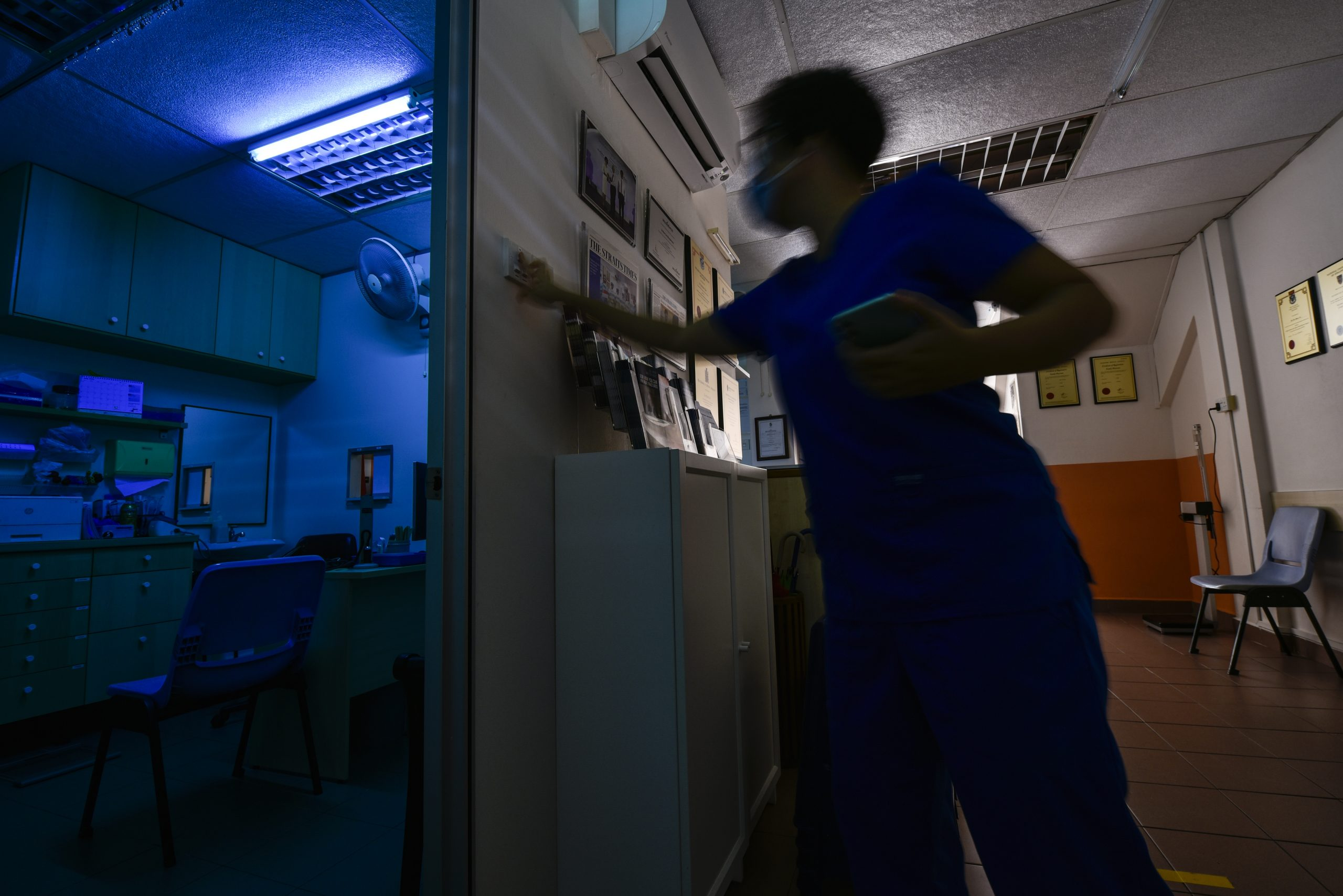 A clinic assistant switches the UVC germicidal lamps on at the end of the day. When the clinic closes, all clinic surfaces are given a thorough wipe-down before these blue lights are turned on. These lamps were strategically placed opposite air-conditioning units so that the circulated air would pass through the blue light for disinfection.