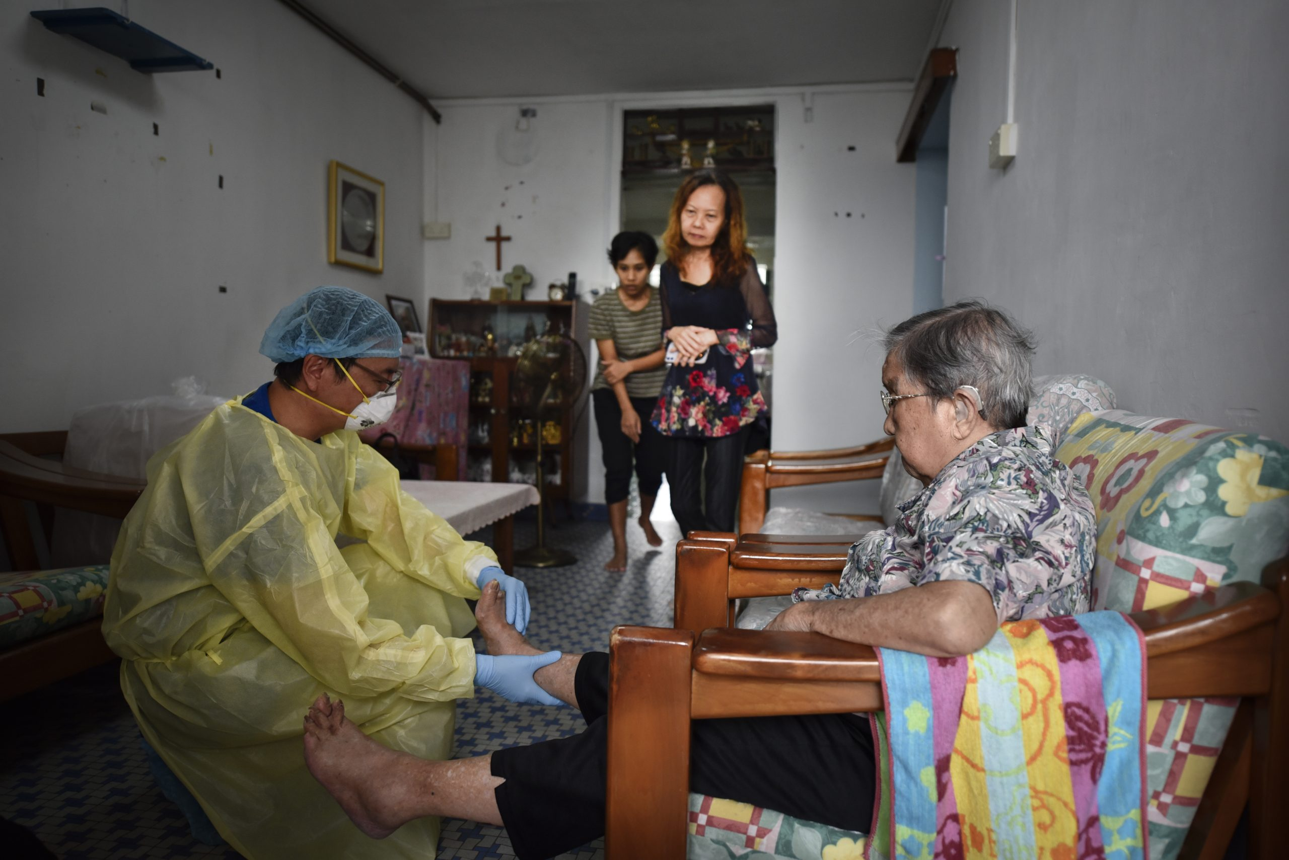 Dr Tham examines Mdm Eng's swollen feet. Most of his patients are elderly, who have been seeing him for many years now.