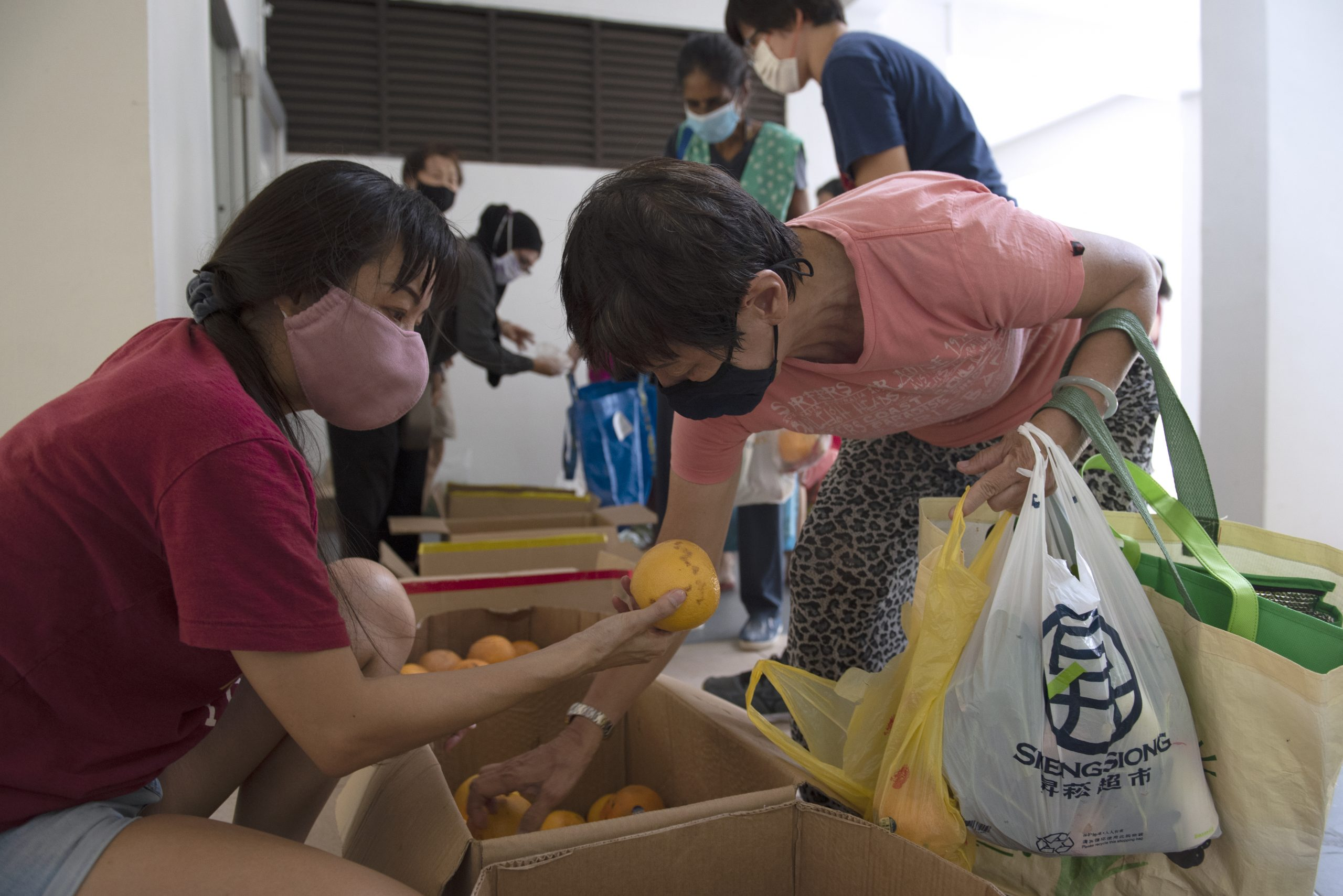 Volunteers helping to distribute rescued fruit and vegetables to residents at Block 20 Marine Terrace, reserving some for those with mobility issues. Residents are encouraged to take only what they need, so that everyone gets some food.