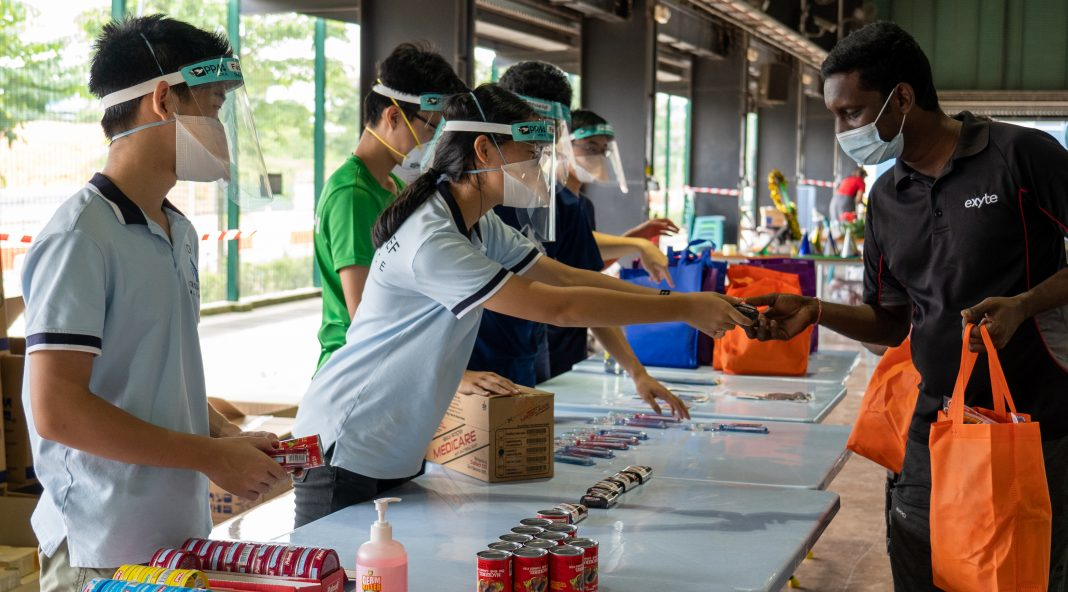 Peace and Daniel Lim, 18 and 15, distribute items to migrant workers